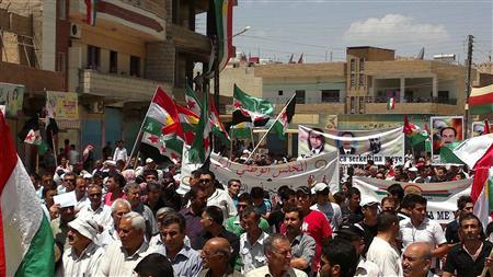 Demonstrators hold Kurdish and opposition flags during a protest against Syria's President Bashar Al-Assad after Friday prayers in Qamishli May 11, 2012. REUTER/Omer Ali/Shaam News Network/Handout