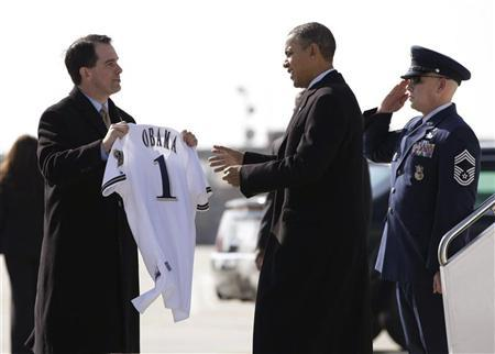 Wisconsin Governor Scott Walker presents U.S. President Barack Obama with a Milwaukee Brewers jersey upon his arrival in Milwaukee, Wisconsin February 15, 2012. REUTERS/Jason Reed