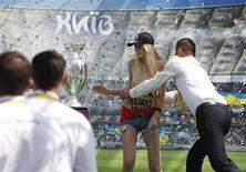 Guardas detêm ativista do grupo pró-direitos das mulheres perto do troféu da Eurocopa de 2012 durante exposição da taça em Kiev. REUTERS/Gleb Garanich