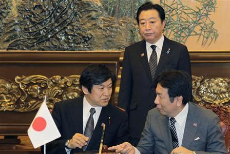Japan's Prime Minister Yoshihiko Noda (back) looks on as Japan's Trade Minister Yukio Edano (R) attends a signing ceremony of the fifth trilateral summit among China, South Korea and Japan at the Great Hall of the People in Beijing, May 13, 2012. Chinese Premier Wen Jiabao urged northeast Asian powers to cooperate more in the face of global economic headwinds, as China, Japan and South Korea agreed at a summit on Sunday to soon launch negotiations on a three-way free trade pact. REUTERS/Petar Kujundzic