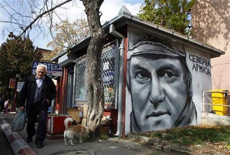 A Kosovo Serb man walks past graffiti of Bosnian Serb wartime general Ratko Mladic in town of Zevecan October 25, 2011. REUTERS/Marko Djurica