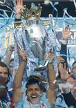 """Игрок """"Манчестер Сити"""" Серхио Агуэро держит кубок чемпионата Англии на стадионе в Манчестере, 13 мая 2012 года. """"Манчестер Сити"""" впервые выиграл золотые медали чемпионата Англии с 1968 года, благодаря двум голам в уже добавленное к матчу время одолев """"Куинз Парк Рейнджерс"""" со счетом 3-2. REUTERS/Phil Noble"""
