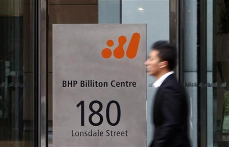 A man walks past the head office of BHP Billiton in central Melbourne. REUTERS/Mick Tsikas