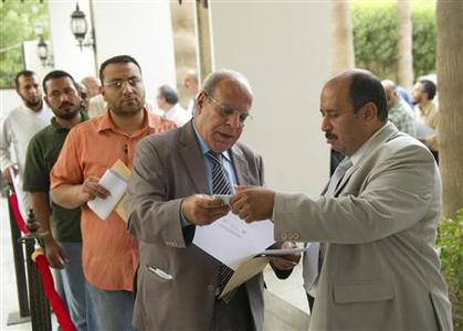 An employee of the Egyptian Embassy checks the voting application of an expatriate Egyptian man before he votes at the embassy in Kuwait May 13, 2012. REUTERS/Stephanie McGehee