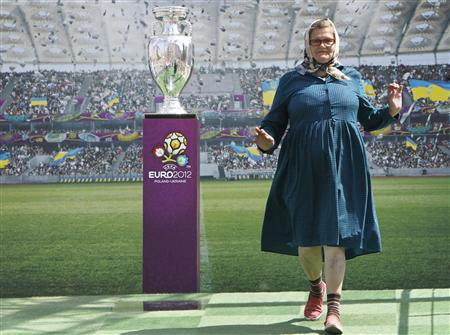 A woman poses for pictures next to the Euro 2012 trophy during a display to the public in central Kiev May 12, 2012. REUTERS/Gleb Garanich