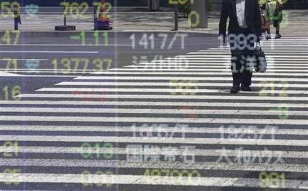 A man is reflected on a stock quotation board outside a brokerage in Tokyo May 11, 2012. REUTERS/Toru Hanai