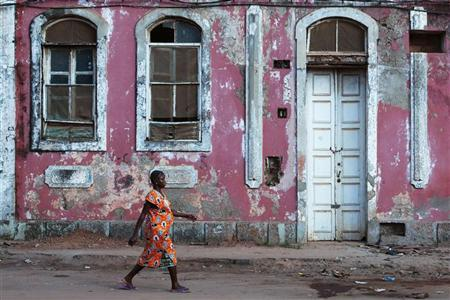 A woman walks past a crumbling colonial building in Guinea-Bissau's capital Bissau March 22, 2012. REUTERS/Joe Penney