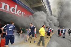 Membros da equipe de Fórmula Um Williams tentam extinguir um incêndio dentro de sua garagem após o Grande Prêmio de Fórmula Um Espanhola no Circuito da Cataluña, próximo a Barcelona, 13 de maio de 2012. REUTERS/Josep Loaso