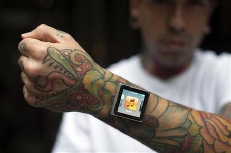 Tattoo artist Dave Hurban displays an iPod Nano which he has attached to his wrists through magnetic piercings in his wrist in New York, May 14, 2012. REUTERS/Keith Bedford