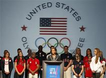 Flanked by U.S. Olympic athletes, First Lady Michelle Obama speaks at the U.S. Olympic Committee Media Summit at the Hilton Anatole in Dallas, Texas May 14, 2012. REUTERS/Darrell Byers