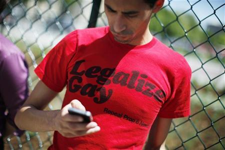 A man checks his mobile phone as civil unions supporters rally in downtown Denver before the Colorado House Judiciary Committee hearing on the Colorado Civil Union Act in Denver May 3, 2012. The bill passed the Colorado Senate last week. REUTERS/Rick Wilking