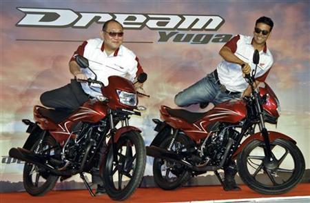 Keita Muramatsu (L), president of Honda's India unit, and Bollywood actor Akshay Kumar mount on newly launched 110cc Dream Yuga motorbikes in Gurgaon on the outskirts of New Delhi May 15, 2012. REUTERS/B Mathur