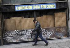 "A man walks past a closed store with a sign reading ""Total clearance closure"" in downtown Madrid April 19, 2012. REUTERS/Andrea Comas"