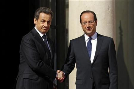 France's outgoing President Nicolas Sarkozy (L) shakes hands with newly-elected President Francois Hollande on the steps of the Elysee Palace at the handover ceremony in Paris May 15, 2012. REUTERS/Benoit Tessier)