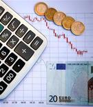 Банкнота в 20 евро лежит на графике около калькулятора в Зенице, 19 октября 2011 года. Еврозона едва избежала рецессии в начале 2012 года, но долговой кризис региона истощил силы Франции и Италии и увеличил разрыв между богатой Германией и проблемными экономиками. REUTERS/Dado Ruvic