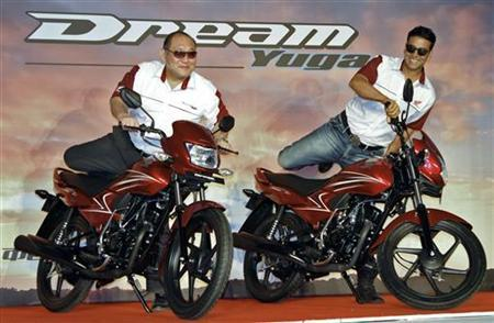 Keita Muramatsu (L), president of Honda's India unit, and Bollywood actor Akshay Kumar mount on newly launched 110cc Dream Yuga motorbikes in Gurgaon on the outskirts of New Delhi May 15, 2012. REUTERS/B Mathur