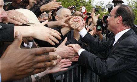 France's new President Francois Hollande (R) shakes hands with supporters on the Champs Elysees Avenue after the handover ceremony in Paris May 15, 2012. REUTERS/Regis Duvignau