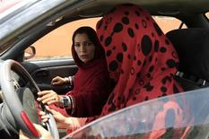 Shakila Naderi (L), teaches a girl how to drive a car, in Kabul May 15, 2012. REUTERS/Mohammad Ismail
