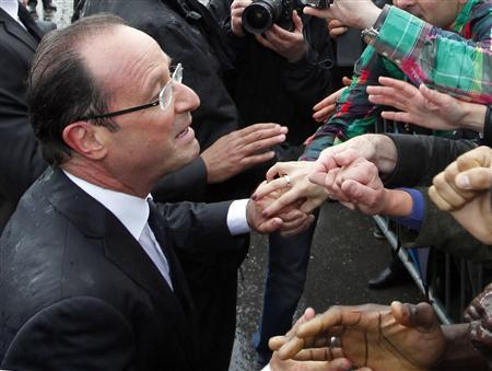 France's new President Francois Hollande (L) shakes hands with supporters on the Champs Elysees Avenue after the handover ceremony in Paris May 15, 2012. REUTERS/Regis Duvignau