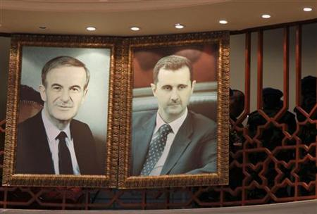 Members of the United Nations observers mission in Syria are seen near portraits of Syrian President Bashar al-Assad (R) and his father, the late president Hafez, at a hotel in Damascus, before heading to the areas where protests against the regime of Bashar al-Assad have been taking place, May 15, 2012. REUTERS/Khaled al-Hariri