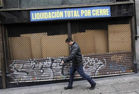A man walks past a closed store with a sign reading ''Total clearance closure'' in downtown Madrid April 19, 2012. REUTERS/Andrea Comas