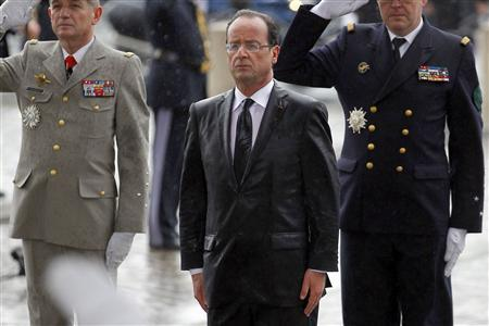 France's new President Francois Hollande (C) stands in the rain as he attends a ceremony at the Arc de Triomphe after his investiture ceremony in Paris May 15, 2012. REUTERS/Regis Duvignau
