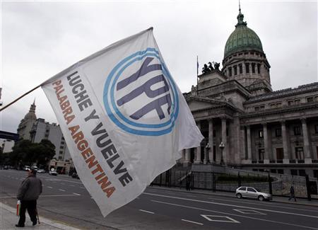A man waves a flag with the YPF logo in front of the Argentine Congress in Buenos Aires April 25, 2012. REUTERS/Marcos Brindicci