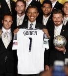 U.S. President Barack Obama holds a team jersey as he poses with members of the 2011 Major League Soccer champions, Los Angeles Galaxy soccer team, in the East Room at the White House in Washington, May 15, 2012. REUTERS/Larry Downing