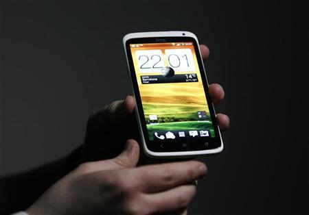A man holds up the new HTC One after a news conference at the Mobile World Congress in Barcelona February 26, 2012. REUTERS/Gustau Nacarino