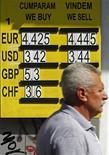 Мужчина проходит мимо пункта обмена валют в Бухаресте, 11 мая 2012 года. Евро колеблется у минимума четырех лет против доллара в среду и, вероятно, увеличит потери на фоне того, что Грецию ожидают новые парламентские выборы, что усиливает риск выхода страны из еврозоны. REUTERS/Bogdan Cristel