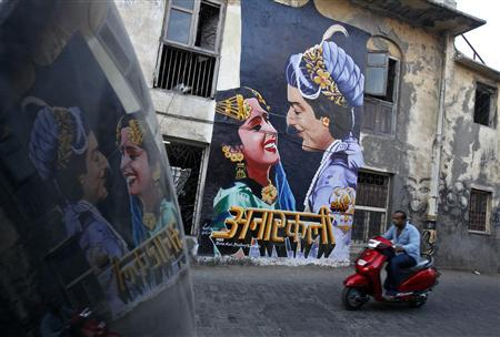 A man rides a motorbike past a mural of the classic Bollywood movie ''Anarkali'' on the wall of a building in Mumbai May 13, 2012. The mural is the brainchild of a pair of movie buffs, Ranjit Dahiya and Tony Peter, who hope to give Mumbai a distinct Bollywood identity through a series of murals, aiming for the iconic appeal of the ''Hollywood'' sign in California. The mural from Anarkali, a 1953 film about a doomed love affair between the prince and a commoner, is just the first of many the pair, and their Bollywood Art Project, hope to create all over the city. Picture taken May 13, 2012. To match story INDIA-BOLLYWOOD/MURAL REUTERS/Vivek Prakash