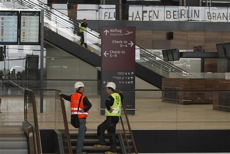 Workers talk in the terminal building of the new Berlin-Brandenburg Airport outside Berlin May 12, 2012. REUTERS/Thomas Peter