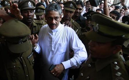 Jailed former army Chief Sarath Fonseka leaves with prison officers at the high court in Colombo January 25, 2011. REUTERS/Dinuka Liyanawatte/Files