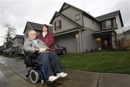 Recent home buyers Robert and Debra Eaton are pictured in front of their home in Spanaway, Washington on April 25, 2012. REUTERS/Anthony Bolante