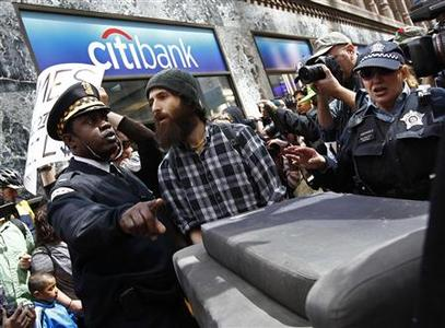 Chicago Police prevent protesters from placing furniture on the sidewalk in front of a bank during one of the demonstrations during the week ahead of the NATO meeting in Chicago, May 16, 2012. REUTERS/Jim Young