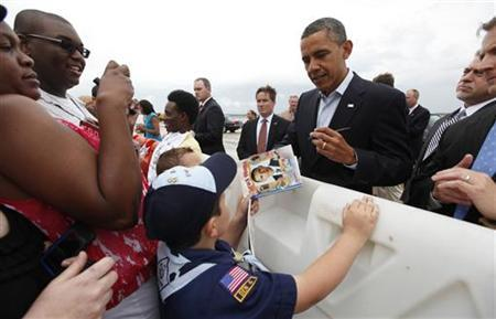 U.S. President Barack Obama signs a book about him for a boy scout upon his arrival in Richmond, Virginia May 5, 2012. REUTERS/Kevin Lamarque