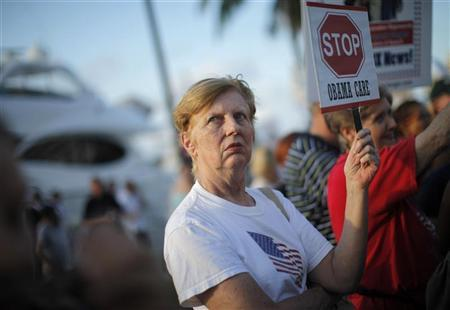A resident of south Florida holds a sign protesting healthcare reforms during a visit by U.S. President Barack Obama to Miami, Florida, October 26, 2009. REUTERS/Carlos Barria
