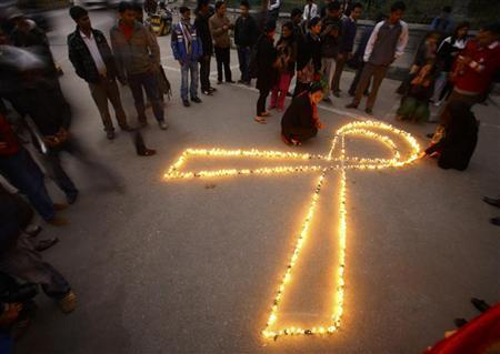 People gather around lit candles to mark the upcoming World AIDS Day in Kathmandu November 30, 2011. REUTERS/Navesh Chitrakar