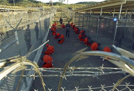 Detainees in orange jumpsuits sit in a holding area under the watchful eyes of military police during in-processing to the temporary detention facility at Camp X-Ray of Naval Base Guantanamo Bay in this January 11, 2002 file photograph. REUTERS/Stringer/Files