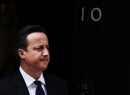 Britain's Prime Minister David Cameron waits to greet Qatar's Prime Minister Sheikh Hamad bin Jassim al-Thani at Downing Street in London May 16, 2012. REUTERS/Luke MacGregor