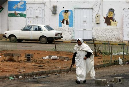 A man walks in front of a wall painted with graffiti depicting toppled Libyan leader Muammar Gaddafi in the town of Zintan February 23, 2012. REUTERS/Ismail Zitouny