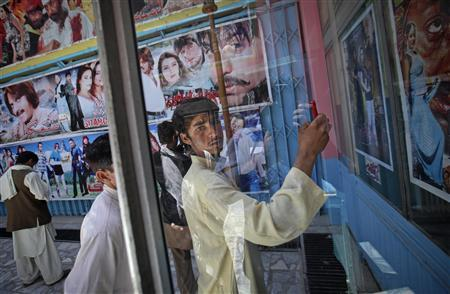 A cinema goer uses his mobile phone to take a photograph of a film poster at Cinema Pamir in Kabul May 4, 2012. Once a treasured luxury for the elite, Afghan cinemas are dilapidated and reflect an industry on the brink of collapse from conflict and financial neglect. Kabul's cinemas show Pakistani films in Pashto, American action films and Bollywood to rowdy, largely unemployed crowds in pursuit of any distraction from their drab surroundings. Picture taken May 4, 2012. REUTERS/Danish Siddiqui