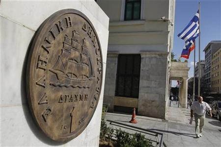 A man makes his way next to a replica of a one drachma coin outside the Athens Town Hall May 15, 2012. REUTERS/Yorgos Karahalis