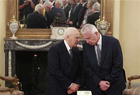 Greece's newly appointed caretaker Prime Minister Panagiotis Pikrammenos (R) talks with President Karolos Papoulias during a swearing-in ceremony at the Presidential palace in Athens May 17, 2012. Greece put a senior judge in charge of an emergency government on Wednesday to lead the nation to new elections on June 17 and bankers tried to calm public fears after the president said political chaos risked causing panic and a run on deposits. REUTERS/John Kolesidis