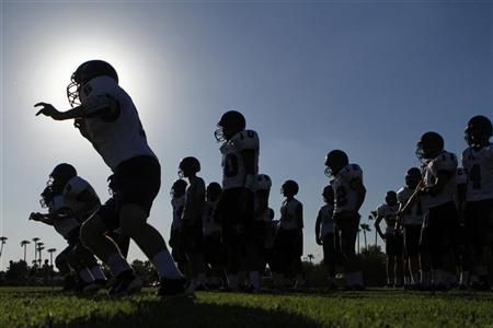A high school football team practices in Tempe, Arizona August 4, 2011. REUTERS/Joshua Lott