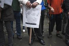 A protester in the Occupy Wall Street movement holds a protest sign with the face of JPMorgan CEO Jamie Dimon as he participates in a rally in New York, May 15, 2012. REUTERS/Keith Bedford