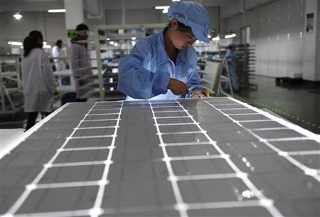 An employee works on a solar panel production line at a solar company workshop in Yongkang, Zhejiang province February 23, 2012. REUTERS/Stringer