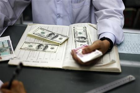A man counts US dollars and Myanmar kyats at a money changer in Yangon March 21, 2012. REUTERS/Soe Zeya Tun