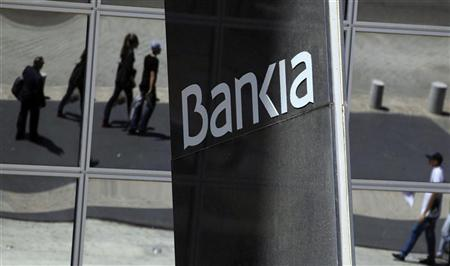 Pedestrians are reflected in the Bankia headquarters building in Madrid, May 10, 2012. REUTERS/Paul Hanna