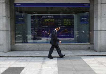 A man walks past a stock quotation board outside a brokerage in Tokyo May 10, 2012. REUTERS/Toru Hanai /Files